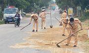 5 chiến sĩ CSGT cùng người dân dọn cát sỏi rơi vãi trên đường