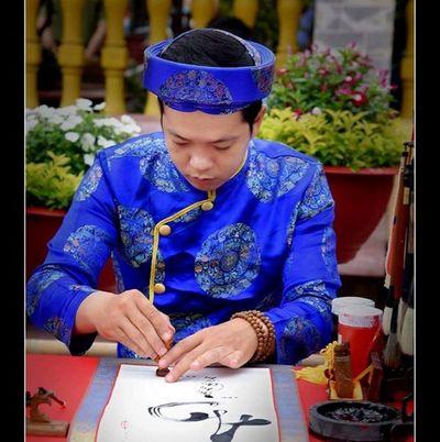 Thầy giáo trẻ đưa bút đề thư pháp trên lá sen khô - ảnh 1