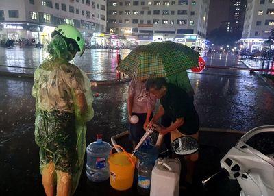 Dân chung cư Hà Nội chen chân, dầm mưa xếp hàng xách từng can nước như thời bao cấp - ảnh 1