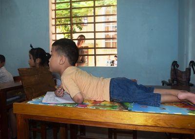 Cậu bé 7 tuổi liệt tứ chi và nghị lực phi thường khi viết chữ bằng miệng - ảnh 1