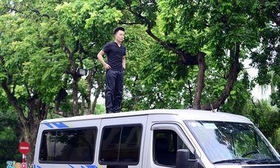 Ảo thuật gia 9X ngồi lơ lửng trên nóc ô tô đọc báo ở Hà Nội