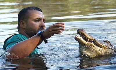 Chàng trai vui đùa với cá sấu 200 kg dưới đầm lầy