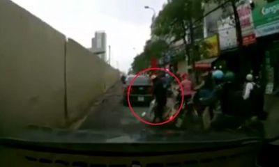 Người phụ nữ bị ngã xe máy vẫn nói chuyện điện thoại