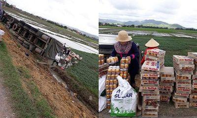 Hình ảnh đẹp: Xe container bị lật, người dân Phú Yên giúp tài xế đưa hàng trăm lon nước lên bờ