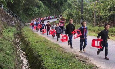 Xúc động hình ảnh trẻ em vùng cao tươi cười xách ghế nhựa, đi bộ đến trường dự lễ khai giảng