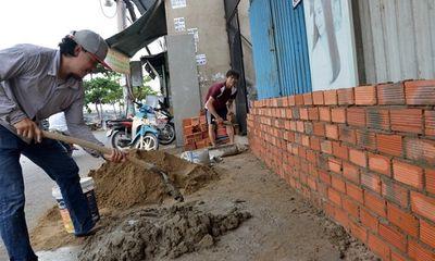 Triều cường dâng cao, người dân TP.HCM hối hả xây tường, đắp bao ngăn nước