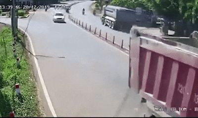 Người đàn ông không đội mũ bảo hiểm, chạy xe máy lấn làn, lạng lách vượt container
