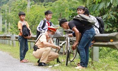 Cảnh sát giao thông sửa xe bên đường cho học sinh