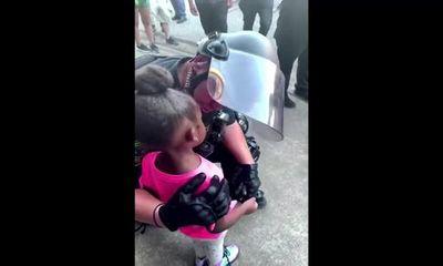 Xúc động khoảnh khắc nam cảnh sát Mỹ ôm bé gái da màu giữa cuộc biểu tình: