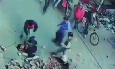 Đang đi bộ, hai người đàn ông bất ngờ bị cả đống gạch rơi xuống đầu