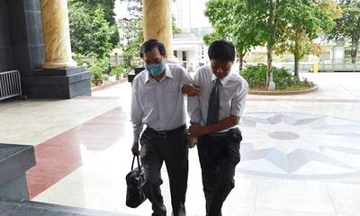 Cựu Bộ trưởng Vũ Huy Hoàng được luật sư dìu bước từng bậc thềm vào tòa