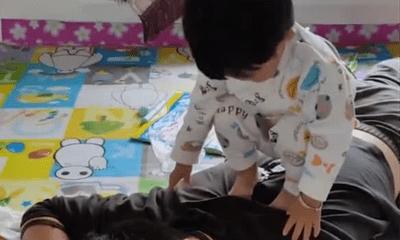 Con gái đứng lên lưng bố, giây sau ngồi thụp xuống làm hành động