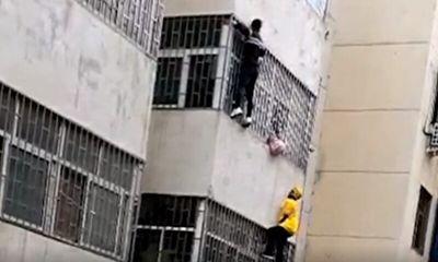 Clip: Nhân viên giao hàng tay không leo 3 tầng lầu cứu đỡ bé gái mắt kẹt ngoài song sắt căn hộ